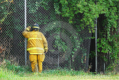 Fireman Peering Through Fence Editorial Photo