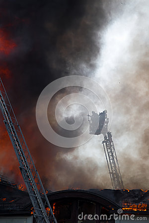 Firemen on a crane over fire roof