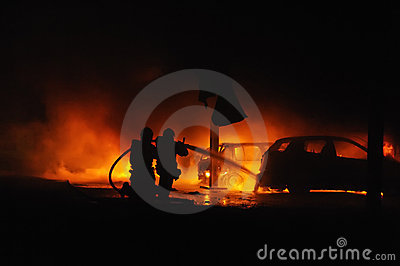 Firemen fighting vehicle fire at night