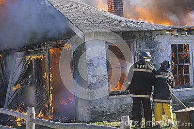 Firemen putting out a house on fire Editorial Stock Photo