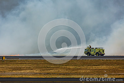 Firemen spray flames as brush fire closes San Salvador International Airport Editorial Photo