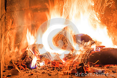 Firewood burning in fireplace fire heat red ashes interior Stock Photo
