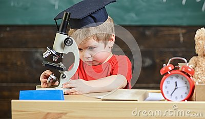 First former interested in studying, learning, education. Kid boy in academic cap work with microscope in classroom Stock Photo