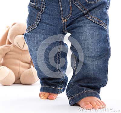 First steps - little baby feets in Jeans isolated on white with