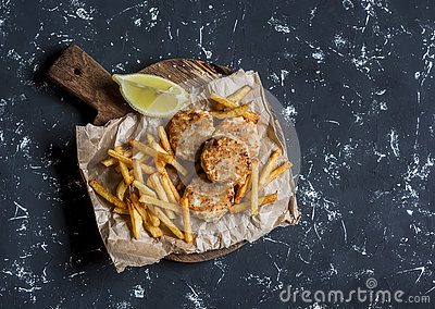Fish balls and potato chips on rustic cutting board on a dark background. Stock Photo
