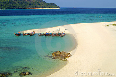 Fish boats on a sandy beach of tropical island