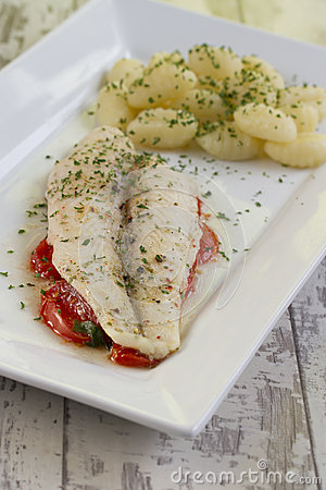 Fish fillet on tomato bed with gnocchi