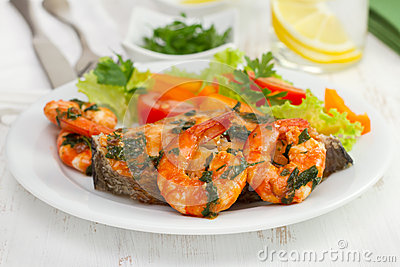 Fish with shrimps and salad on the plate