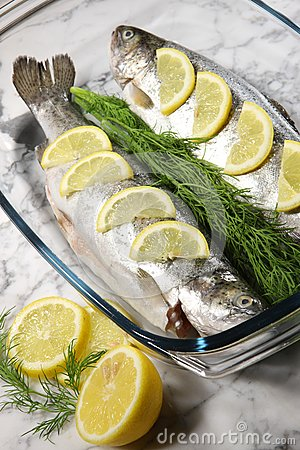 Fish on a white plate with lemons and dill