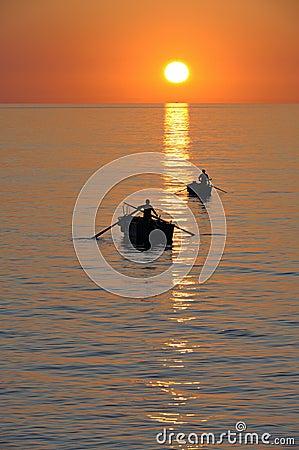 Fisherman on beautiful calm bay at sunrise