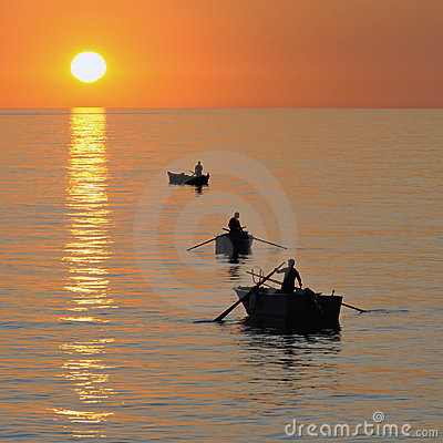 Fisherman on beautiful calm bay at sunrise