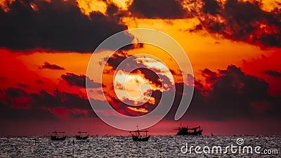 Fisherman on the boat over dramatic sunrise