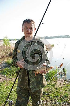 Fisherman holding carp on the shoreline