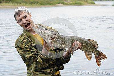Fisherman holds big pike