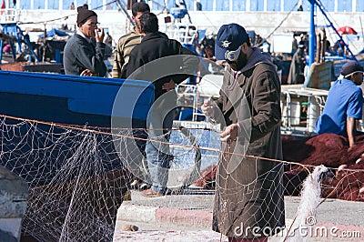 Fisherman repairs net in Essaouira Editorial Stock Image
