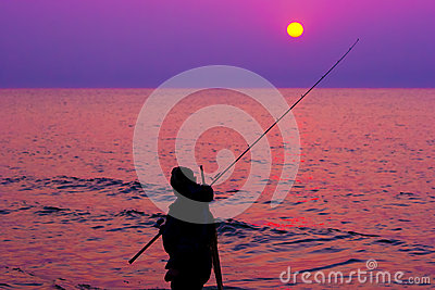 Fisherman by the sea at sunset