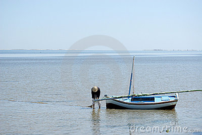 Fisherman in straw hat preparing boat to sail out