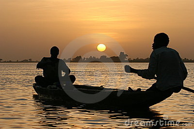 Fishermen crossing a lake at sunset