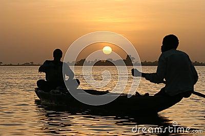 Fishermen crossing a lake at sunset