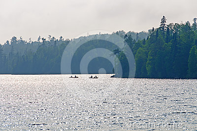Fishermen in evening haze in the wilds