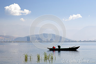 Fishermen on Lake in front of City Editorial Image