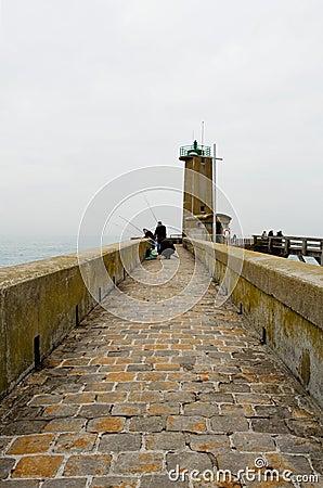 Fishermen on pier near a beacon light