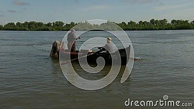 Fishermen releasing fishing net in Danube delta stock video footage