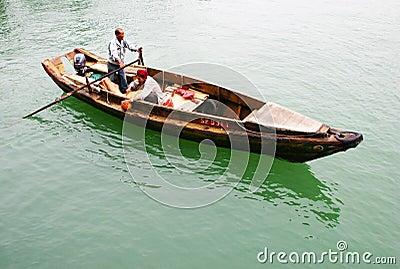 Fishermen rowing in a sampan Editorial Stock Image