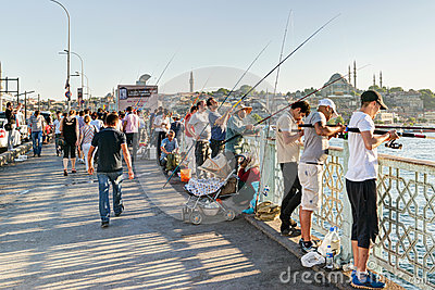 Fishermen and tourists are on the Galata Bridge on may 26, 2013 Editorial Photography