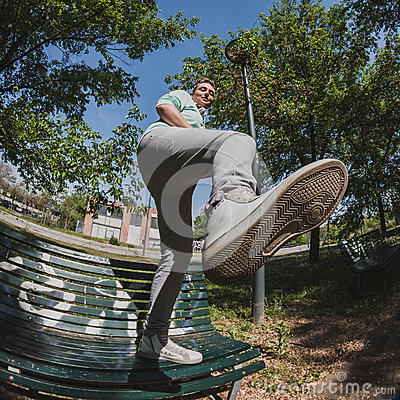 Fisheye shot of short hair girl standing on a bench Stock Photo