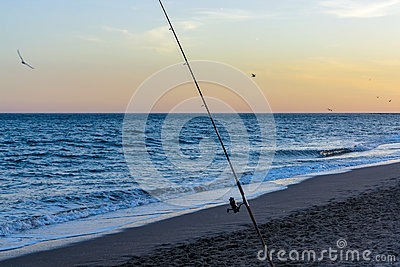 Fishing on the beach at sunset