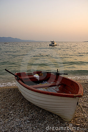 Fishing boat on beach at sunset
