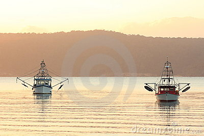 Fishing boats in bay at sunrise