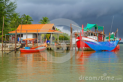 Fishing boats at the river before storm