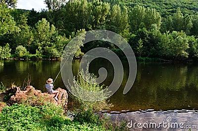 Fishing boy by river
