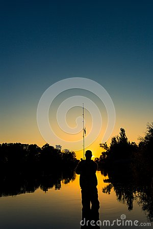Free Fishing On The Lake At Sunset. Silhouette Of A Fisherman. Royalty Free Stock Image - 110087576