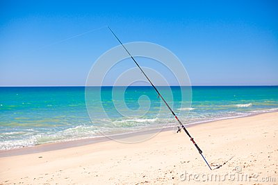 Fishing rod in white sand on tropical beach,