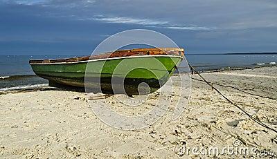 Fiskebåt på den sandiga stranden, Lettland, Europa