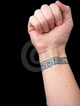 FIST WITH WRIST TATTOO IN GREEK KEY PATTERN OVER BLACK BACKGROUND (click