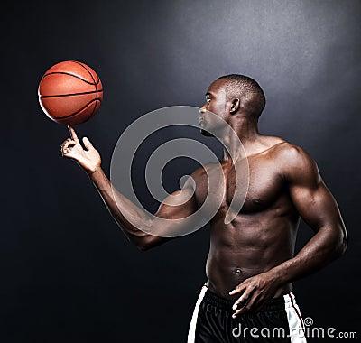 Fit afroamerica man spinning a basketball