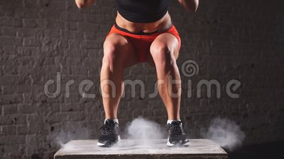 Fit athletic woman does box jumps in the deserted factory gym. Intense exercise is part of her daily cross fitness. Training Program stock footage