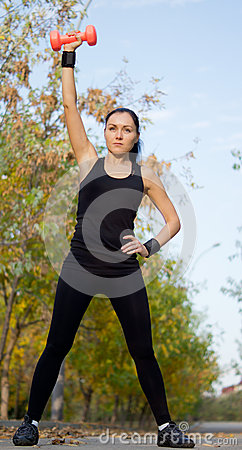 Fit athletic woman exercising with a dumbbell