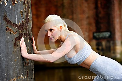 Fit athletic woman stretching against a wall