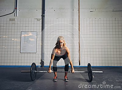 fit female athlete performing a deadlift stock photo