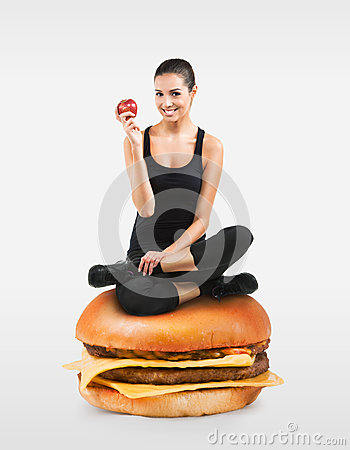Free Fit Girl Sitting On A Hamburger Holding An Apple Royalty Free Stock Photo - 34470185