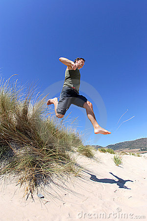 Fit, healthy middle aged man leaping over sand dunes