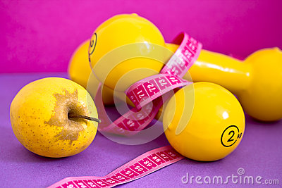 Fit life: dumbbells, measuring tape and apple