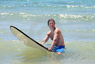 Fit middle aged man surfing on beach in summer