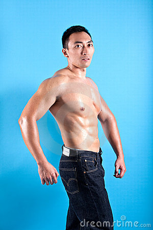 Fit and muscular Asian man in black denim