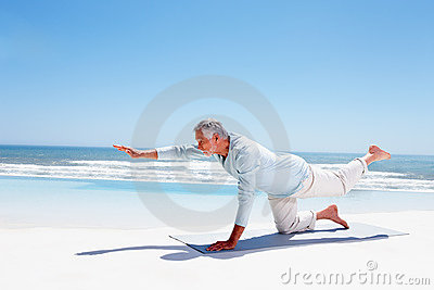 Fit old man practicing yoga on the beach